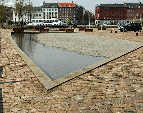 Dokken blev opfyldt i 1918, men dens omrids er markeret i belægningen på stedet, hvor den lå.