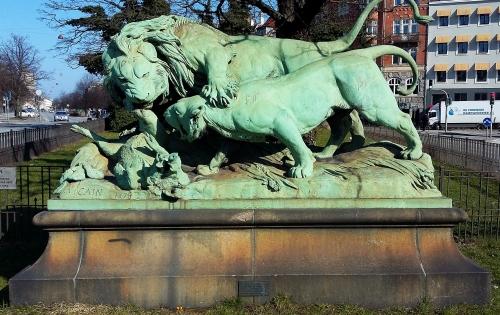 """Foran det lille anlæg, hvor ruinen af Jarmers Tårn ligger, blev der i 1889 opstillet en skulptur med titlen """"Løve og løvinde i kamp om et vildsvin. Den er udført af den franske billedhugger Augste Caïn."""